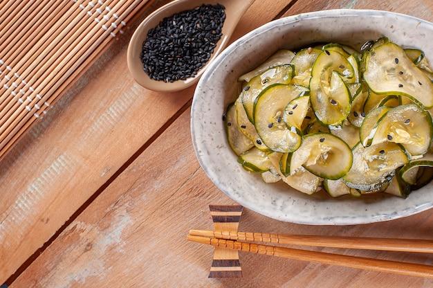 Tradycyjna sałatka kuchni japońskiej o nazwie sunomono. zrobione z ogórka i czarnego sezamu. widok z góry. skopiuj miejsce