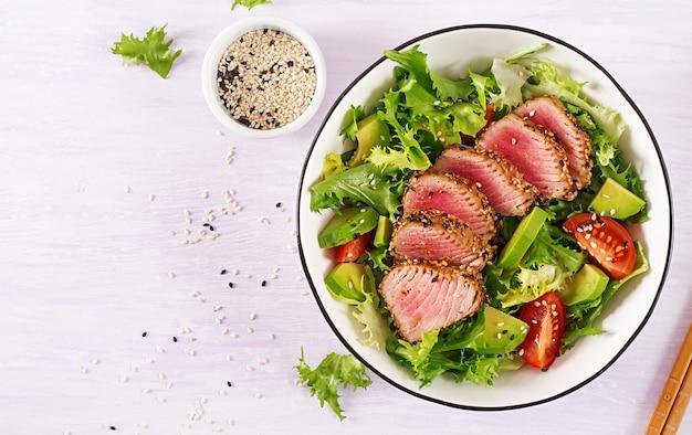 Tradycyjna sałatka z kawałkami średnio rzadkiego grillowanego tuńczyka ahi i sezamu z sałatką ze świeżych warzyw