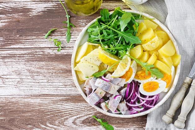 Tradycyjna sałatka z solonego fileta śledziowego, jajek, świeżych jabłek, czerwonej cebuli i ziemniaków.