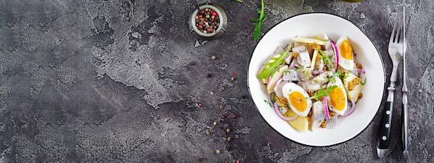 Tradycyjna sałatka z solonego fileta śledziowego, świeżych jabłek, czerwonej cebuli i jajek.