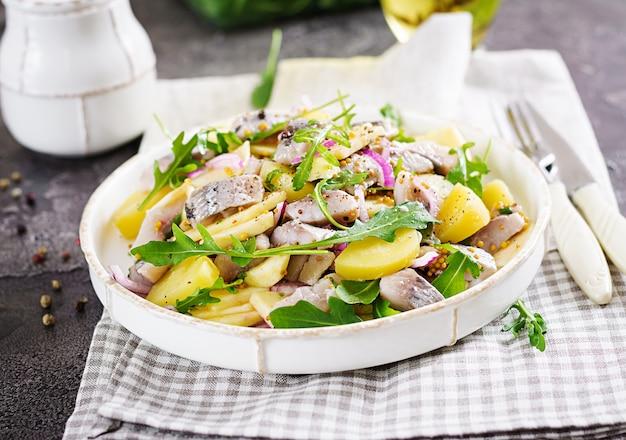 Tradycyjna sałatka z solonego fileta śledziowego, świeżych jabłek, czerwonej cebuli i ziemniaków.