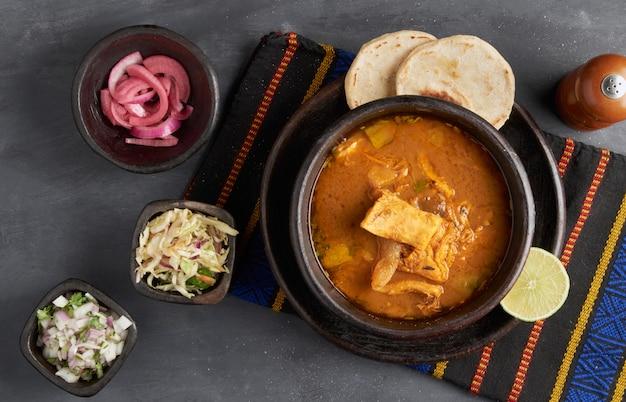 Tradycyjna salwadorska zupa z wołowiną i wnętrznościami podawana z tortillami cytrynowymi, cebulowo-kukurydzianymi, kuchnia ameryki łacińskiej