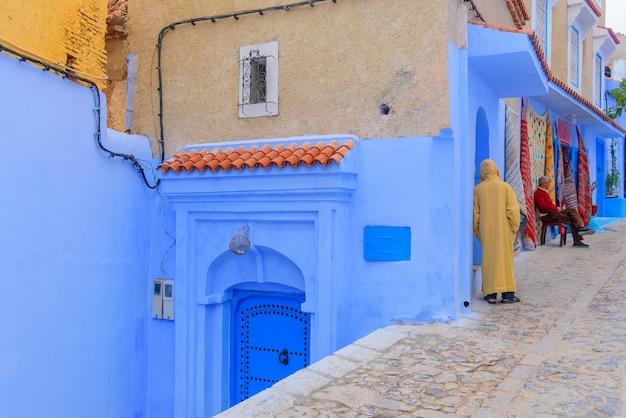 Tradycyjna scena z ludźmi przechodzącymi przez ulicę z niebieskimi fasadami wioski chefchaouen