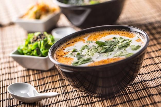 Tradycyjna tajska zupa tom yum z krewetkami i mlekiem kokosowym.