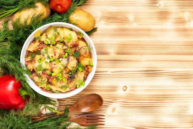 Tradycyjna tartiflette z boczkiem, ziołami i warzywami na drewnianym stole. skopiuj miejsce.