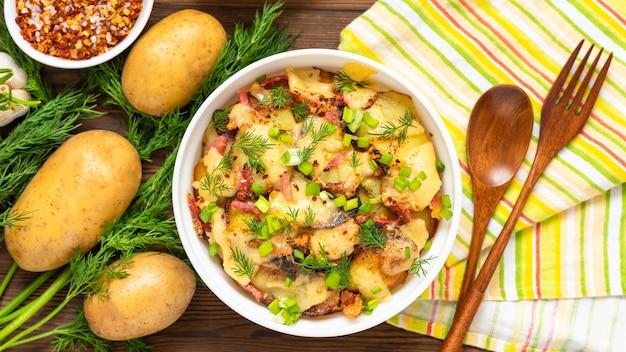 Tradycyjna tartiflette z boczkiem, ziołami i warzywami na drewnianym stole. widok z góry.