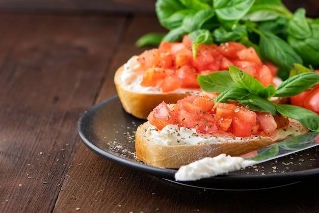 Tradycyjna tostowa bruschetta z włoskich pomidorów z przyprawami i bazylią na ciemnym drewnie.