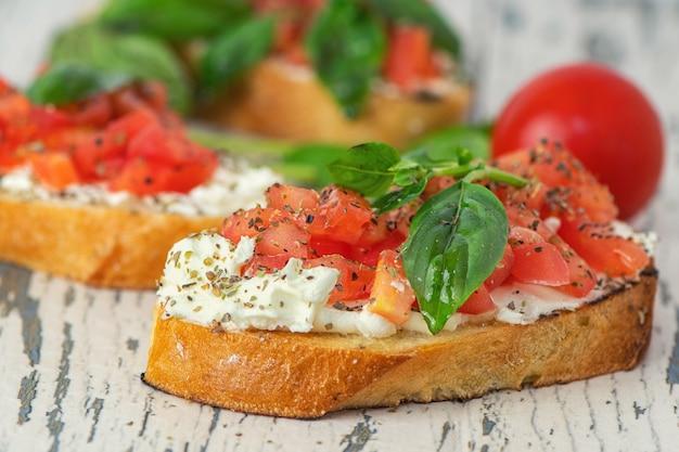 Tradycyjna tostowa bruschetta z włoskich pomidorów z przyprawami i bazylią na jasnym drewnie.