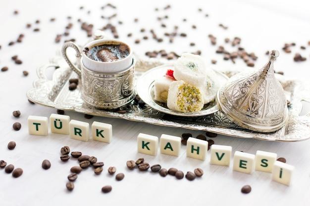 Tradycyjna turecka kawa i słodycze w sztućcach. napis - kawa po turecku - w języku tureckim