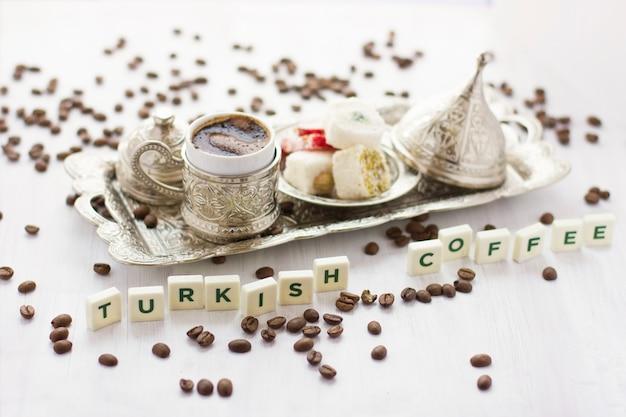 Tradycyjna turecka kawa i słodycze w sztućcach. napis kawa po turecku