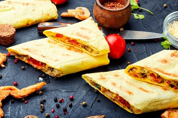 Tradycyjna turecka shawarma z kurczakiem, serem i grzybami.