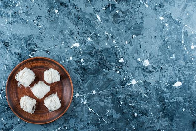 Tradycyjna turecka wata cukrowa na drewnianym talerzu, na niebieskim stole.