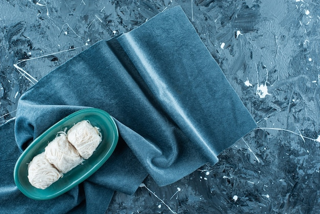 Tradycyjna turecka wata cukrowa na talerzu na ręczniku, na niebieskim stole.