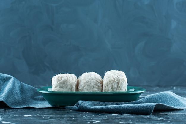 Tradycyjna turecka wata cukrowa na talerzu na ręczniku, na niebieskim tle.