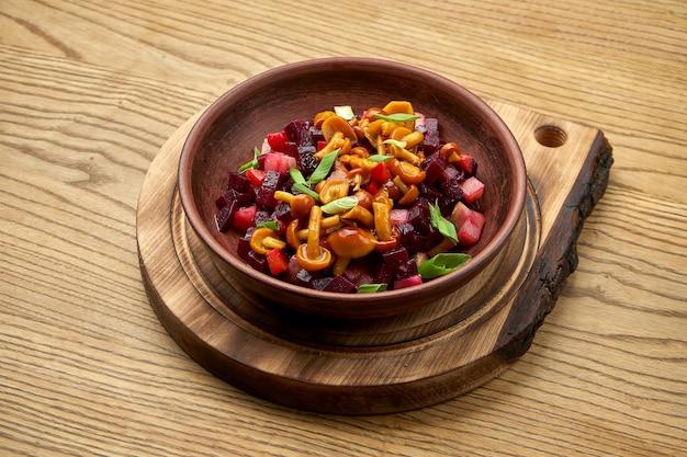 Tradycyjna ukraińska sałatka z buraków, ziemniaków, cebuli, ogórków kiszonych, podawana w misce na drewnianym stole