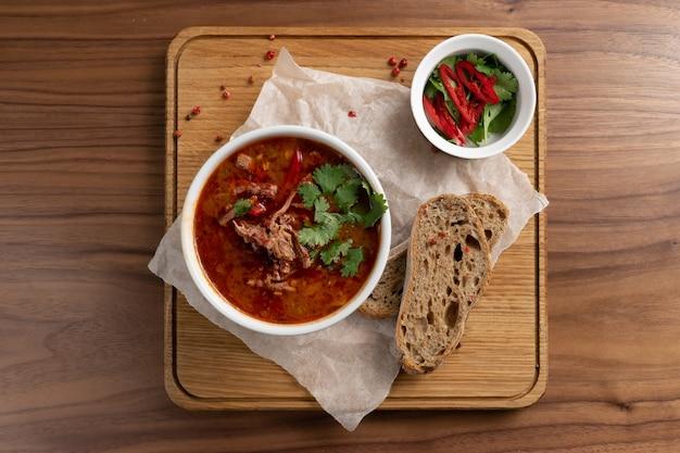 Tradycyjna ukraińska zupa z buraków, warzyw i mięsa z pieczywem na drewnianym stole. widok z góry.