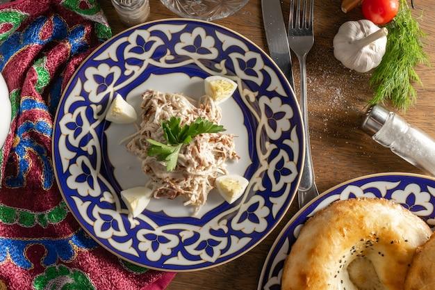 Tradycyjna uzbecka sałatka z taszkientu z wołowiny, rzodkiewki daikon i smażonej cebuli, gotowanego jajka i pietruszki na talerzu ceramicznym z tradycyjnymi uzbeckimi zdobieniami na drewnianym stole.