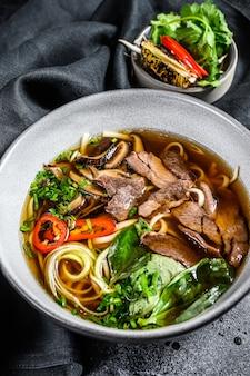 Tradycyjna wietnamska zupa pho bo z mięsem z ziołami, makaron ryżowy, bulion