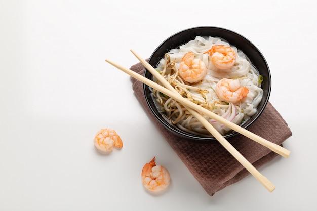Tradycyjna wietnamska zupa z makaronem pho z krewetkami w czarnej misce