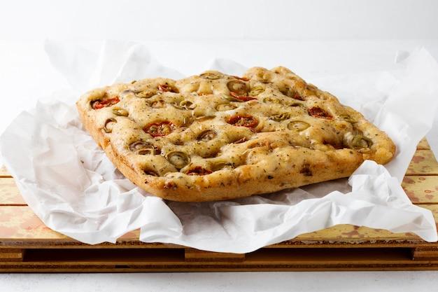 Tradycyjna włoska focaccia z pomidorami i oliwkami