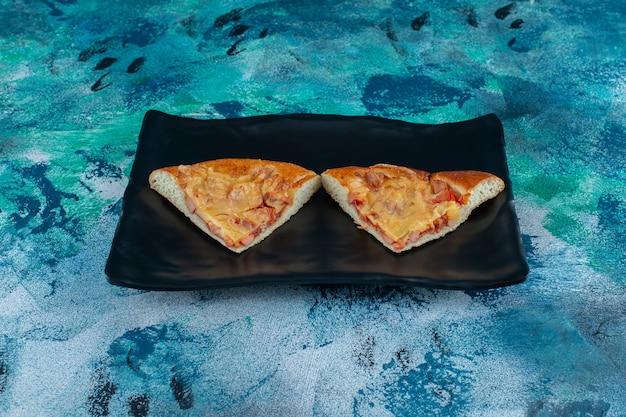 Tradycyjna włoska mini pizza na drewnianym talerzu, na marmurowym stole.