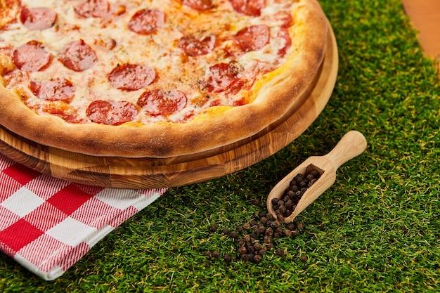 Tradycyjna włoska pizza pepperoni z salami, mozzarellą i bazylią na zielonej trawie