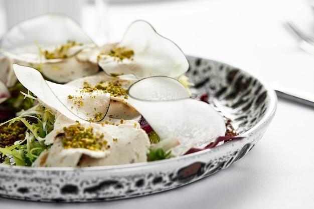 Tradycyjna włoska przystawka vitello tonnato z cienko pokrojonej marynowanej cielęciny, doprawionej sosem śmietanowym i tuńczykiem.