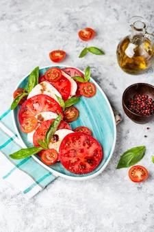 Tradycyjna włoska sałatka caprese z plastrami pomidorów, mozzarellą, bazylią, oliwą