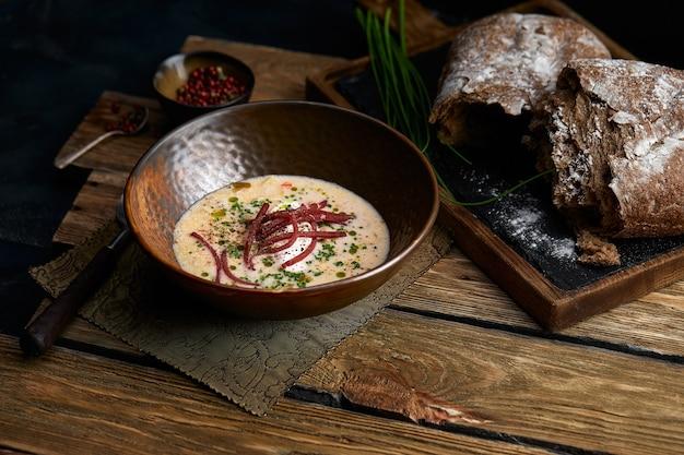 Tradycyjna włoska zupa z jęczmienia i bresaola na stare drewniane tła. selektywne skupienie. ciemny ton.