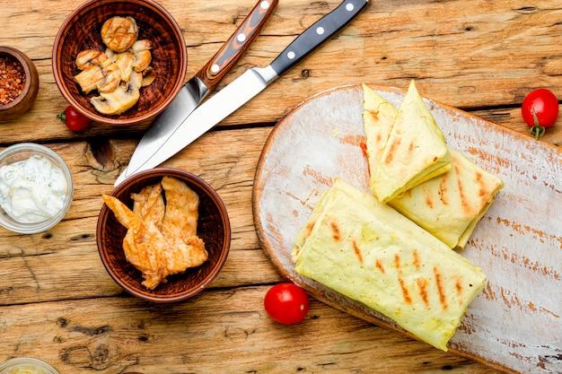 Tradycyjna wschodnia shawarma z kurczakiem, serem i grzybami na desce kuchennej