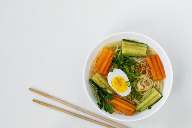 Tradycyjna zupa azjatycka z makaronem, marchewką, cukinią i jajkiem na białym tle