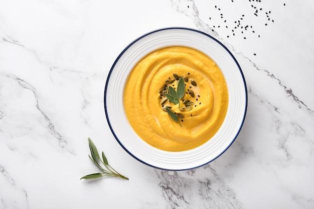 Tradycyjna zupa dyniowa o kremowej, jedwabistej konsystencji z liśćmi szałwii i czerwonym pieprzem w białym talerzu lub misce. jasnoszarym tle. skopiuj miejsce. makieta. widok z góry, układ płaski.