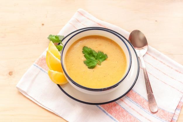 Tradycyjna zupa z soczewicy w białym talerzu na drewnianym stole