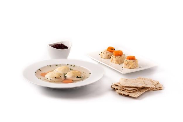 Tradycyjna żydowska zupa kulkowa macy, gefilte ryby i chleb macy na białym tle