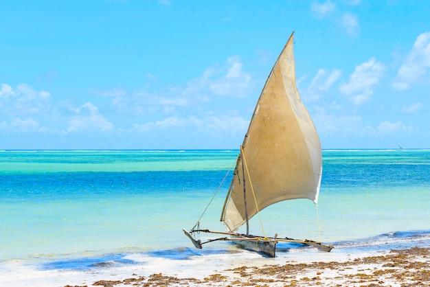 Tradycyjne afrykańskie łodzie z litego drewna pod żaglami na brzegu oceanu indyjskiego z turkusową wodą na wyspie