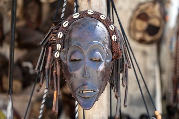 Tradycyjne afrykańskie maski drewniane wiszące na sprzedaż na targu ulicznym na wyspie zanzibar, tanzania, afryka wschodnia, z bliska