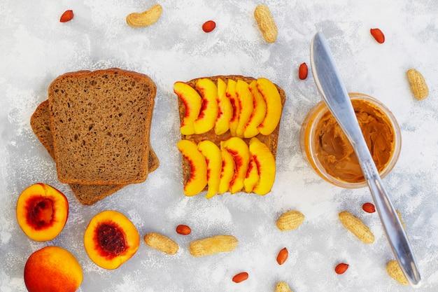 Tradycyjne amerykańskie i europejskie letnie śniadanie: kanapki tostowe z masłem orzechowym, widok z góry