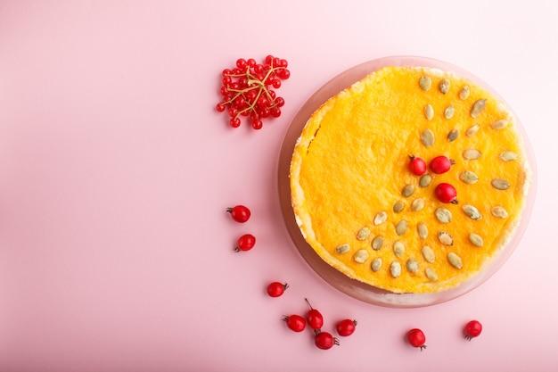 Tradycyjne amerykańskie słodkie ciasto z dyni ozdobione głogowymi czerwonymi jagodami i pestkami dyni na różowym pastelowym tle