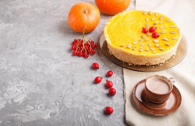 Tradycyjne amerykańskie słodkie ciasto z dyni ozdobione głogowymi czerwonymi jagodami i pestkami dyni z filiżanką kawy na szarym betonowym tle. widok z boku, kopia przestrzeń.