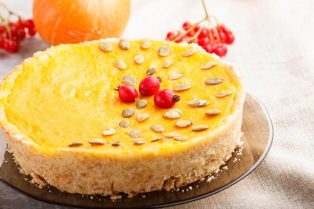 Tradycyjne amerykańskie słodkie ciasto z dyni ozdobione głogowymi czerwonymi jagodami i pestkami dyni z filiżanką kawy na szarym betonowym tle. widok z boku, selektywne focus.