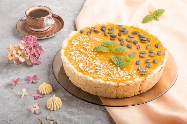 Tradycyjne amerykańskie słodkie ciasto z dyni ozdobione miętą, sezamem i pestkami dyni na szarej betonowej powierzchni. widok z boku, z bliska.