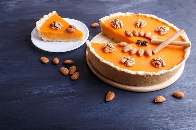 Tradycyjne amerykańskie słodkie ciasto z dyni ozdobione orzechami, na ciemnym niebieskim tle drewnianych.
