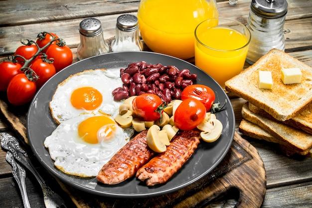Tradycyjne angielskie śniadanie. jajka sadzone z fasolą, kiełbasą i pieczywem smażonym. na drewnianej powierzchni.