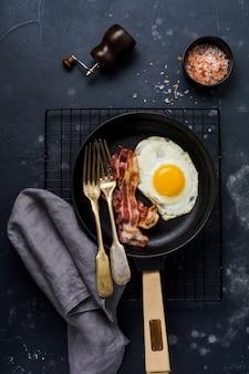 Tradycyjne angielskie śniadanie z jajkiem sadzonym i boczkiem w żeliwnej patelni na ciemnym tle betonu. widok z góry.