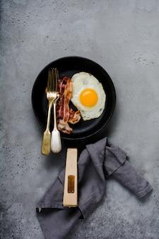 Tradycyjne angielskie śniadanie z jajkiem sadzonym i boczkiem w żeliwnej patelni na starym szarym tle betonu. widok z góry.