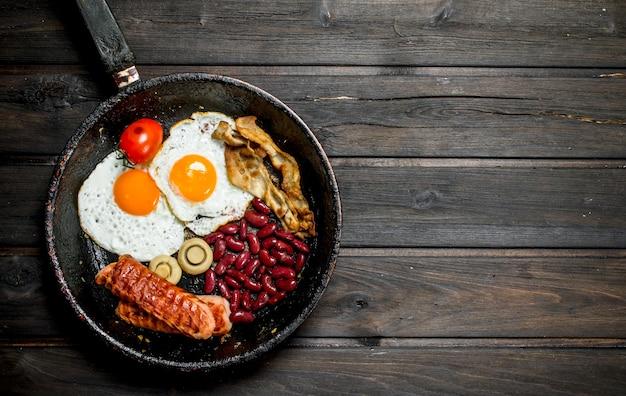 Tradycyjne angielskie śniadanie ze smażonymi jajkami, kiełbasą i fasolą. na drewnianym tle.