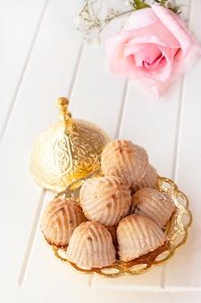 Tradycyjne arabskie ciasto maamoul lub ciastko z daktylami lub orzechami nerkowca lub orzecha włoskiego lub migdałów lub pistacji. wschodnie słodycze. ścieśniać. biała drewniana przestrzeń.