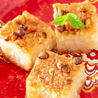 Tradycyjne arabskie ciasto z kaszy manny basbousa lub namoora z orzechami i kokosem. zbliżenie. selektywne ustawianie ostrości. kwadratowe zdjęcie.