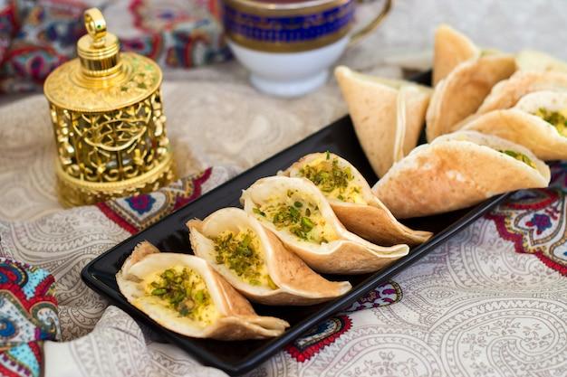 Tradycyjne arabskie naleśniki kataif nadziewane śmietaną i pistacjami, przygotowane na iftar w ramadanie, oud w złocie, na paisley