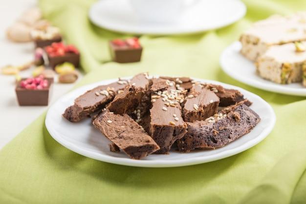 Tradycyjne arabskie słodycze chałwa sezamowa z czekoladą i pistacjami oraz filiżanką kawy. widok z boku